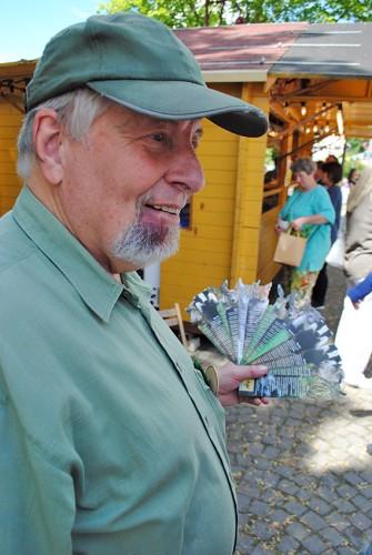 Vereinsvorsitzender Herbert Bachmann bietet Dorffestbesuchern Lesezeichen mit Wildtier-Bildern an.